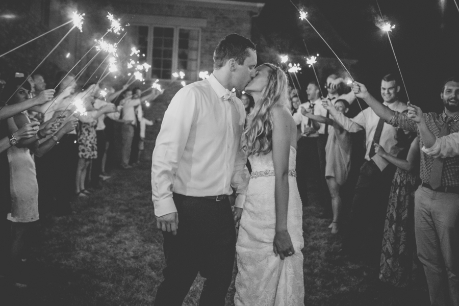 bride and groom under sparkler tunnel
