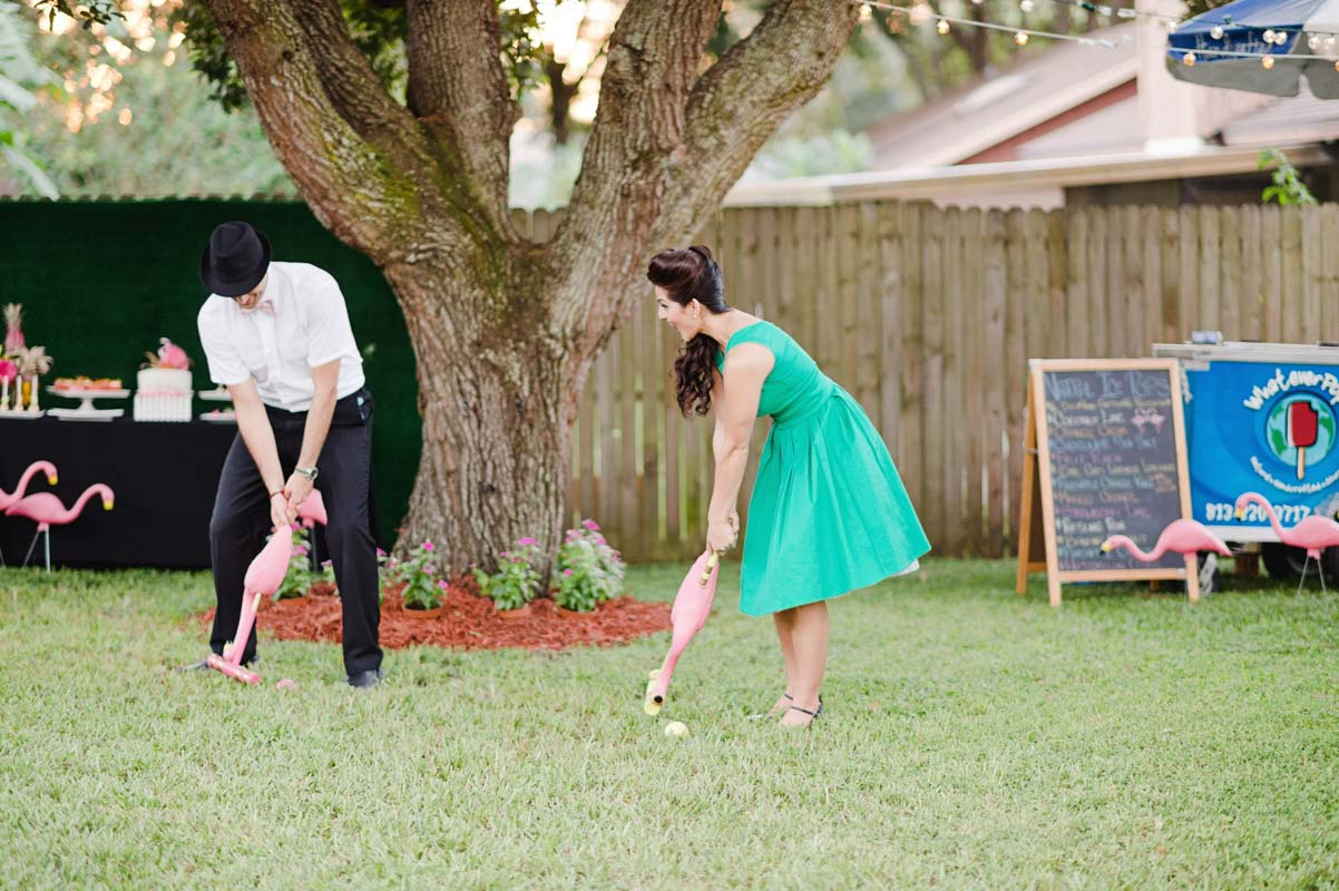 couple playing flamingo themed croquet at engagement party
