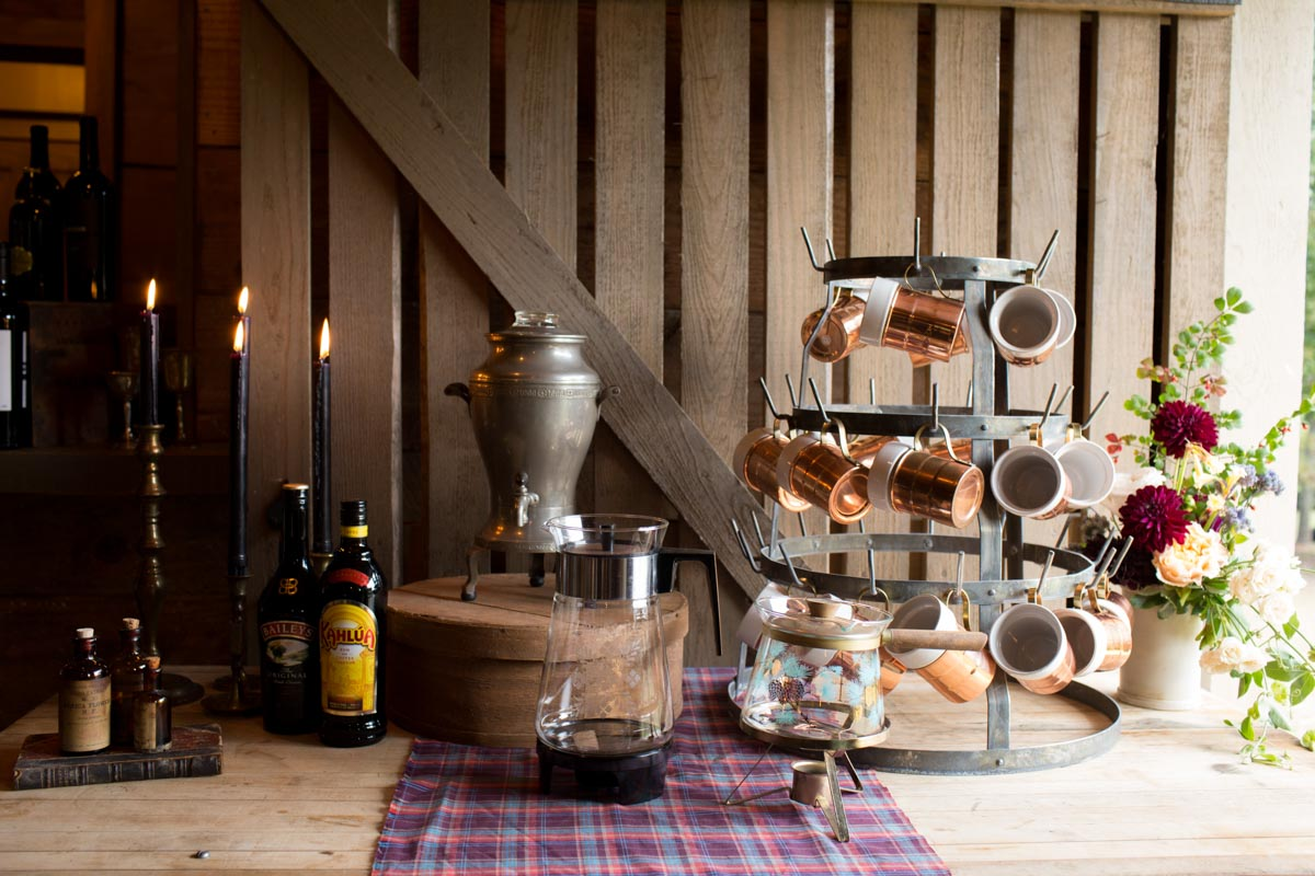 drink station with copper mugs and plaid table runner
