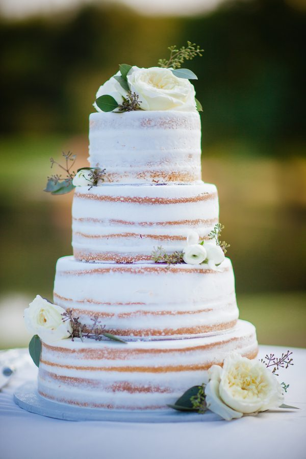 rustic looking wedding cake with white flowers