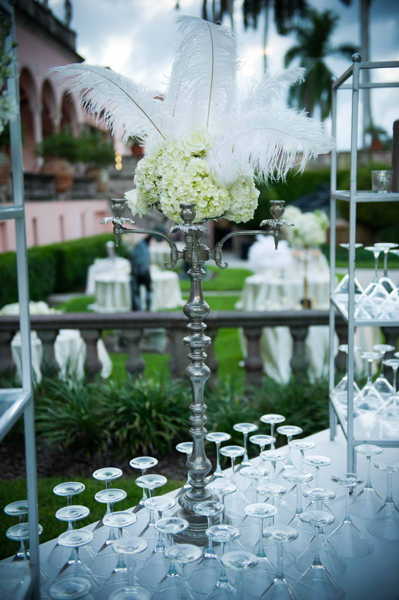 tall silver center piece with hdrangeas and white feathers