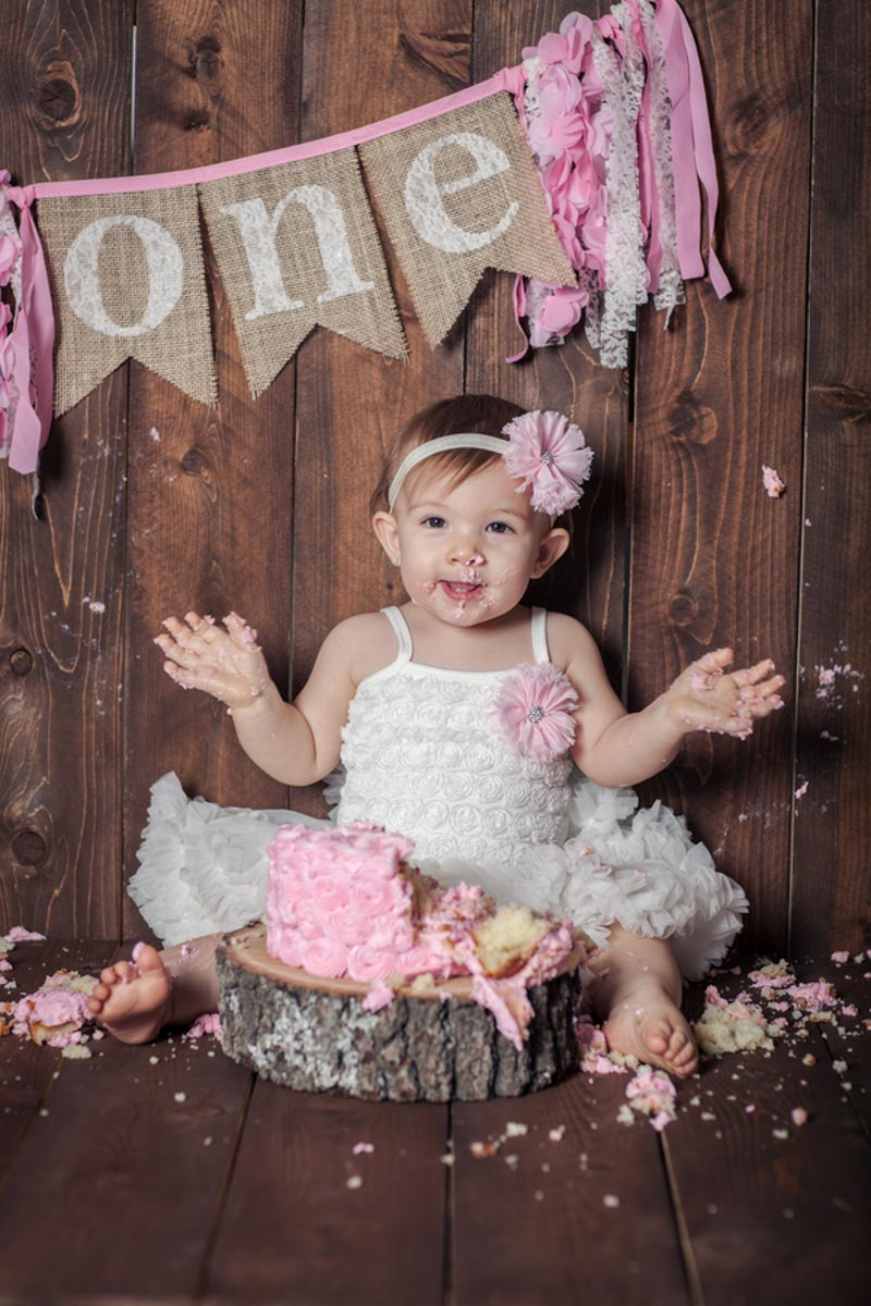 baby on her first birthday with smash cake
