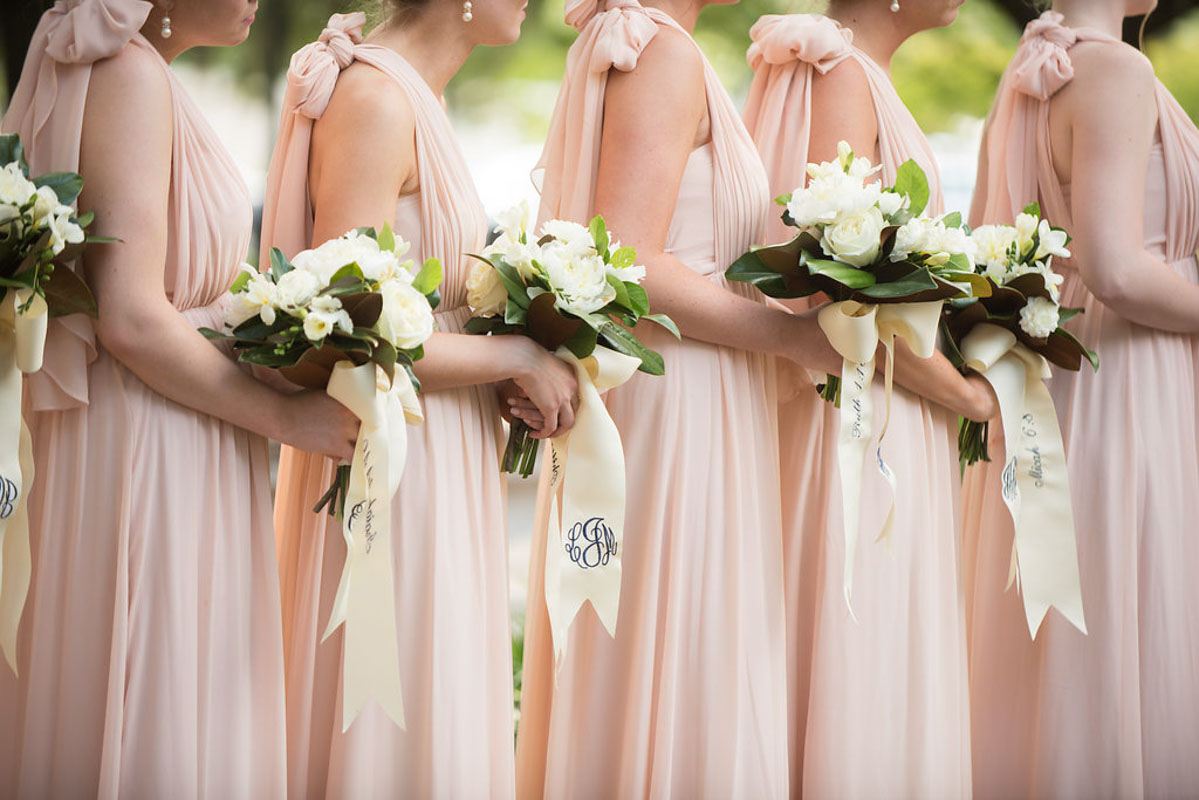 bridesmaids holding bouquets of roses