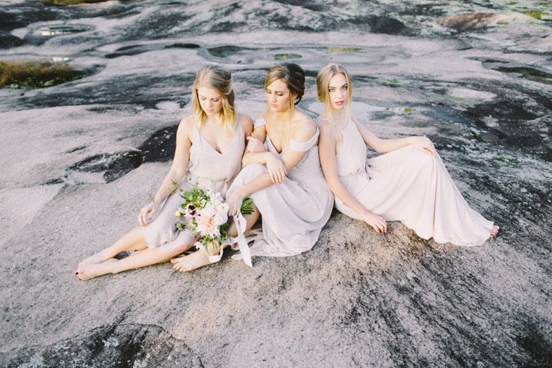 Bride & Bridesmaids Sitting on Rock_