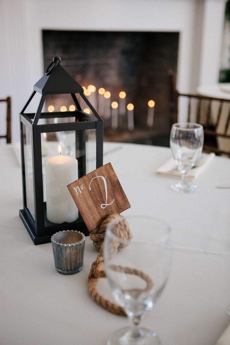Black lantern table centerpiece nautical table number candle fire place Hunter_Gibney_Ais_Portraits_AisPortraitsGibneyRibaultWedding665