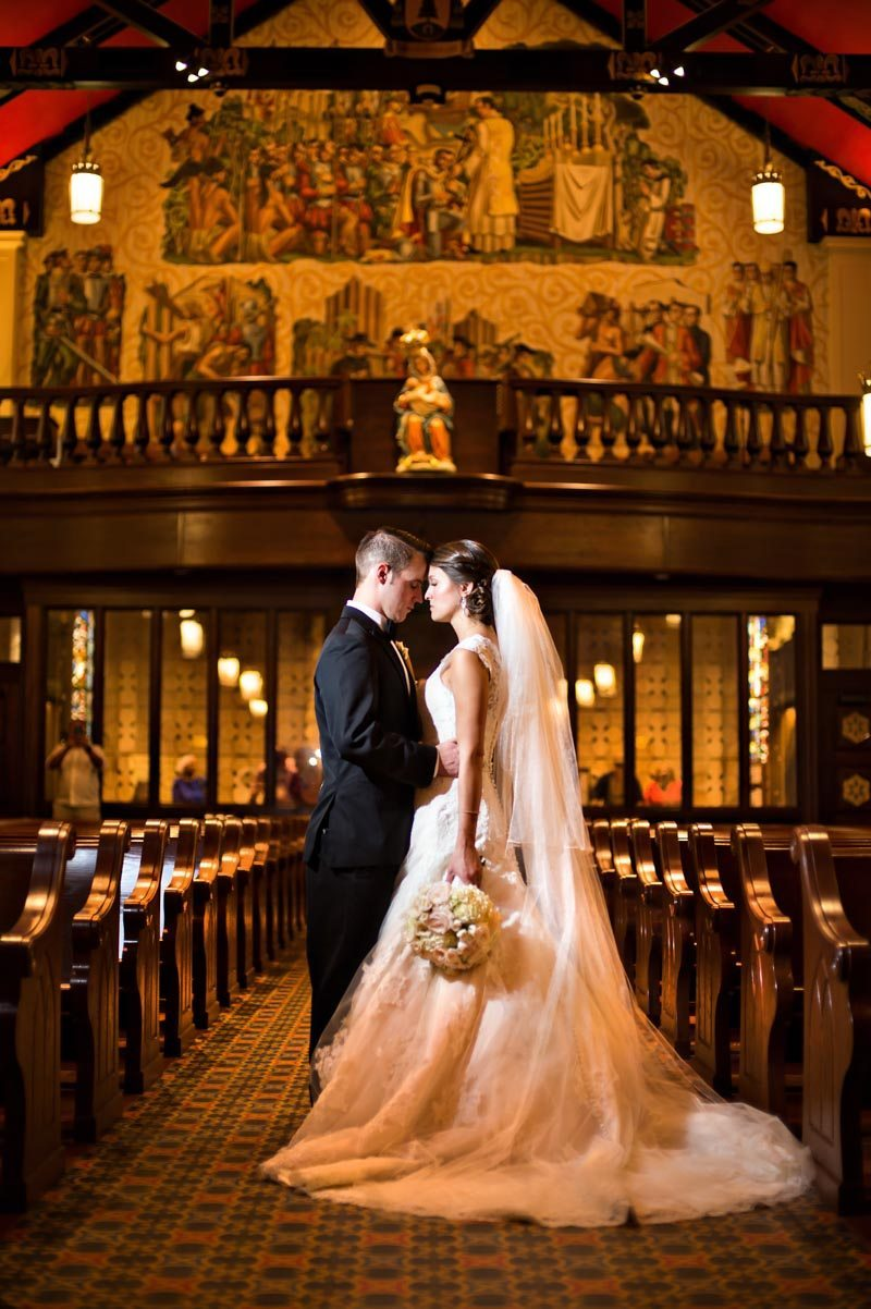 Bride and groom forehead to forehead inside church featuring gold background 11-14-15 Tara and Justin 47