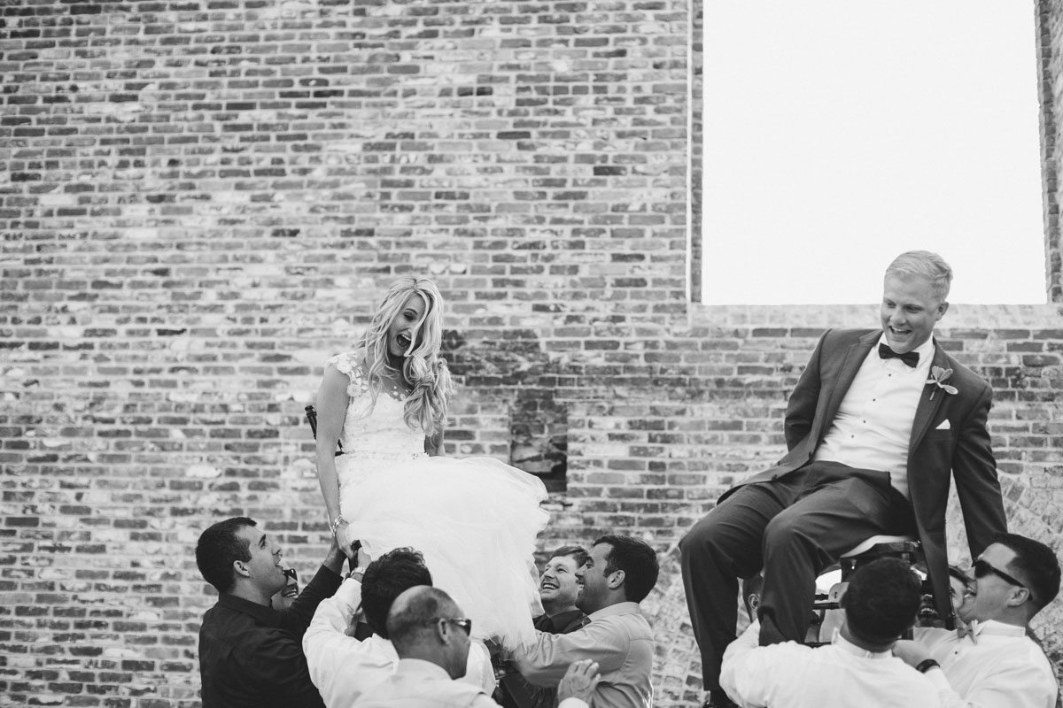 Bride and groom hoisted up on men shoulders in chairs ErinStephan_449
