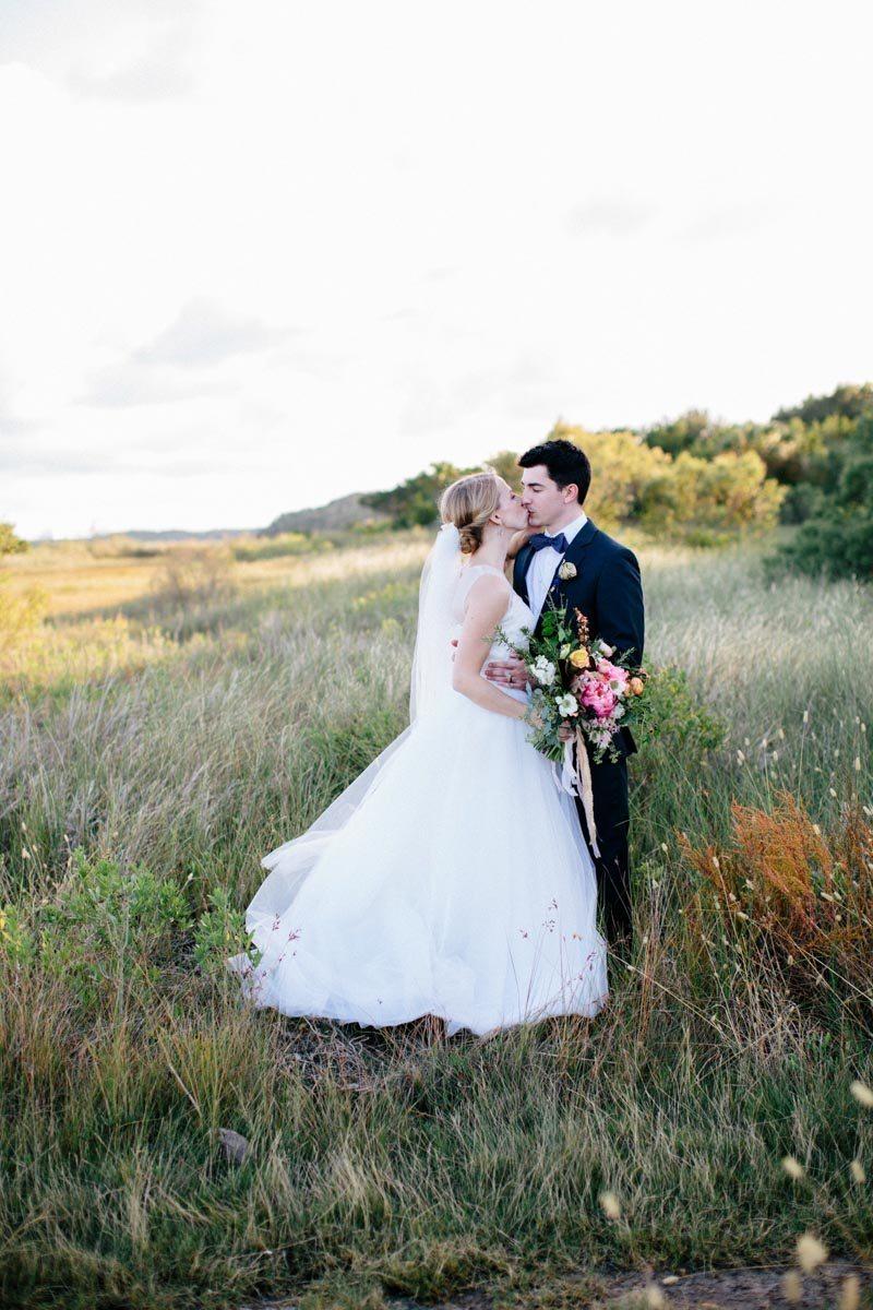 Bride and groom kissing outdoors in grassy weeds longshot Hunter_Gibney_Ais_Portraits_AisPortraitsGibneyRibaultWedding585