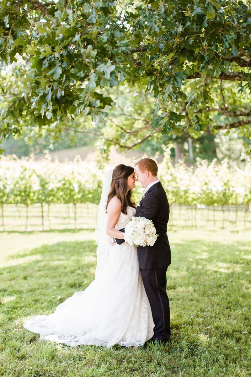 Bride and groom outside on grass touching foreheads