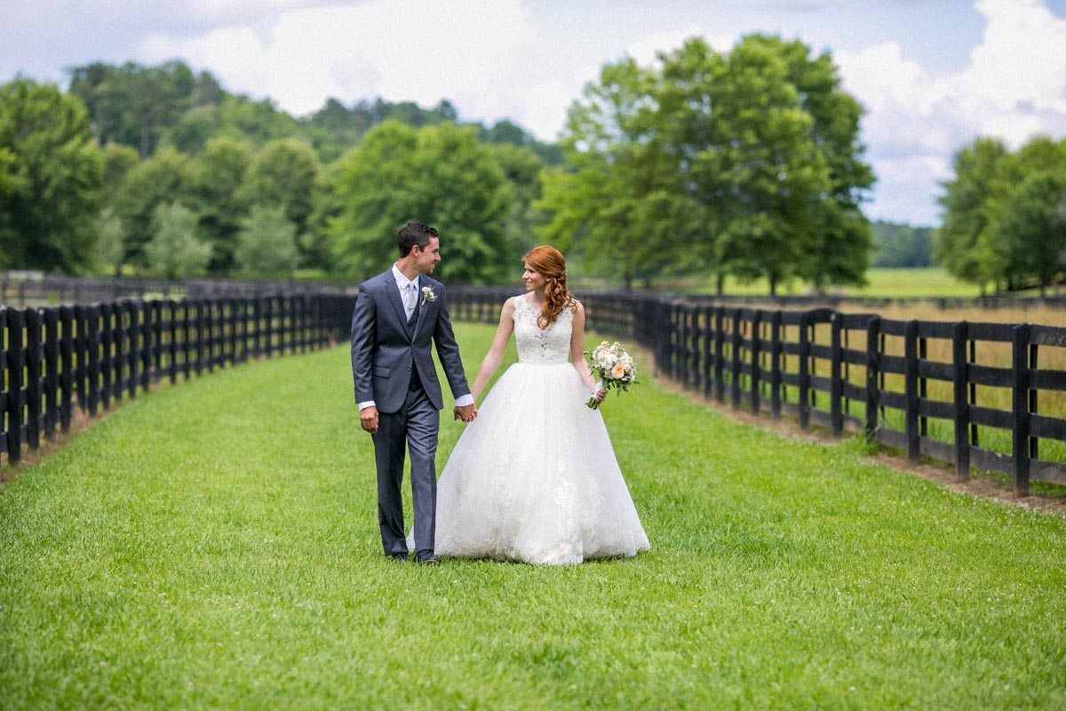 Bride and groom walking together in fieldWeatherby_Weatherby_Jessica_Williams_Studio_Weatherby7199