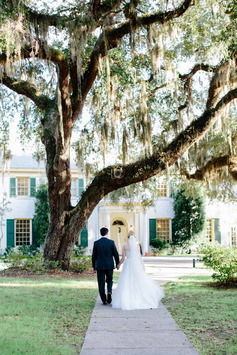 Bride and groom walking toward mansion tree overview Hunter_Gibney_Ais_Portraits_AisPortraitsGibneyRibaultWedding513