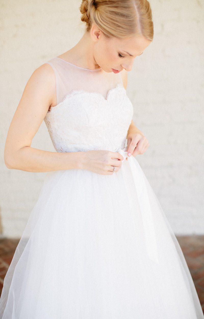 Bride getting ready tying bow on tulle dress Hunter_Gibney_Ais_Portraits_AisPortraitsGibneyRibaultWedding54