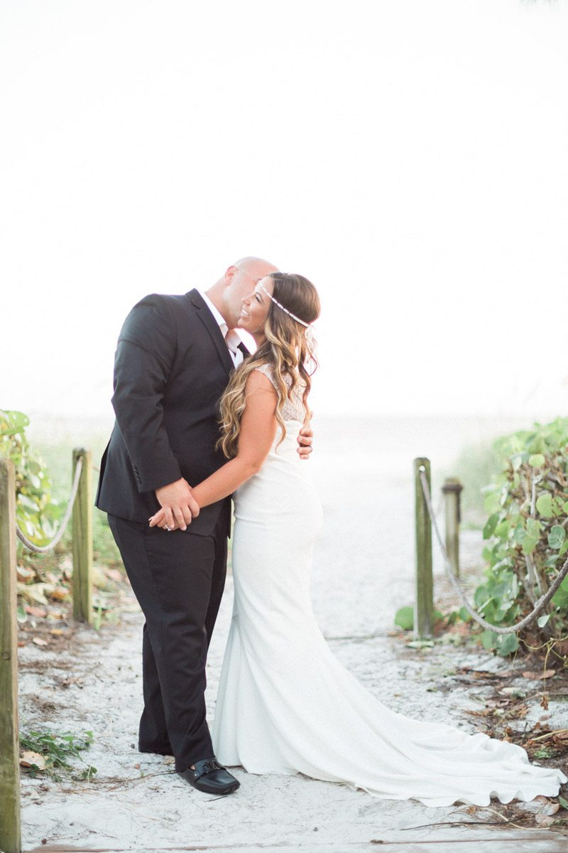 Bride hair beach waves white headpeice feature as groom makes her laugh Mirtich_Scordos_Hunter_Ryan_Photo_sanibelislandcasaybelweddingphotographyhunterryanphoto9027