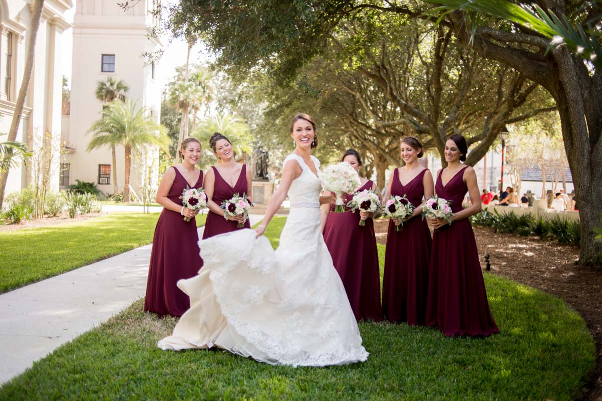 Bride holding dress while bridesmaids in floor length v neck plum gowns look on 11-14-15 Tara and Justin 30