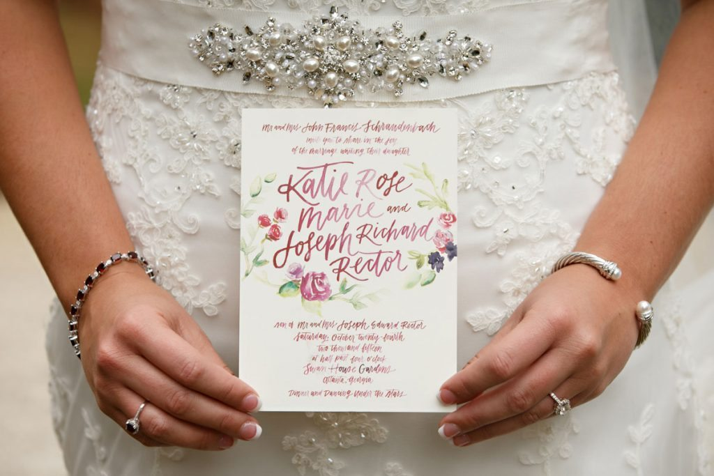 Bride holding invitation and beaded belt featured Schraudenbach_Rector_Laura_Stone_20151024010156