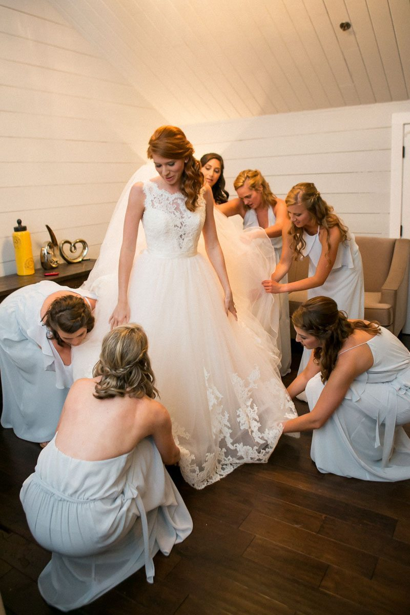 Bridesmaids helping bride put on dress Weatherby_Weatherby_Jessica_Williams_Studio_Weatherby7130