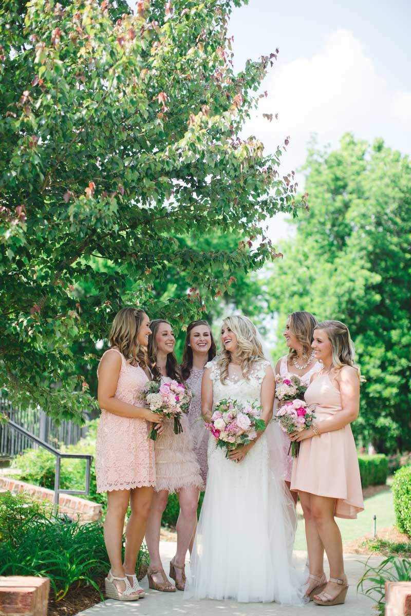 Bridesmaids in mis matched knee length soft pink dresses looking at bride outside ErinStephan_140