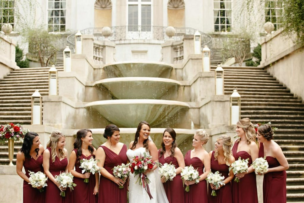 Bridesmaids in one shoulder and v neck red gowns with fountain in background and stairs Schraudenbach_Rector_Laura_Stone_20151024010263
