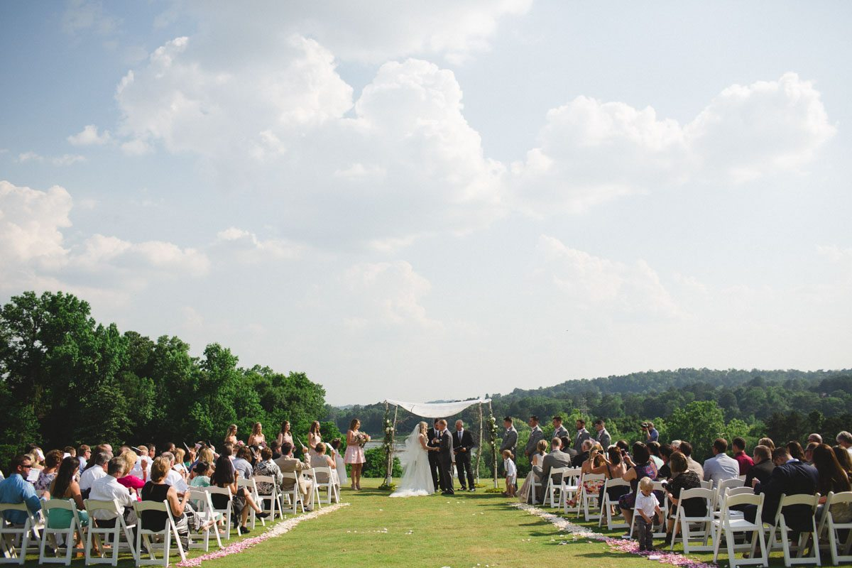 Ceremony space long shot green grass cloudy sky white garden cahirs and lake view in background ErinStephan_233