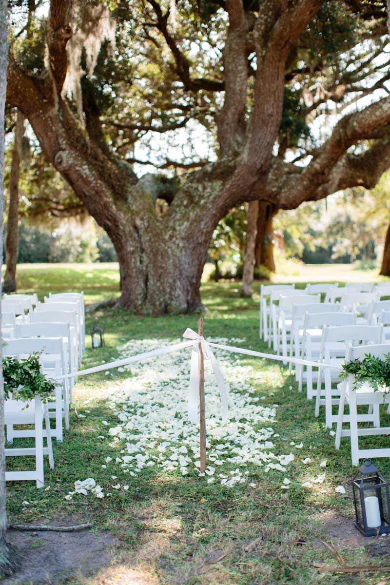 Ceremony under tree white garden chairs and flower petal aisle Hunter_Gibney_Ais_Portraits_AisPortraitsGibneyRibaultWedding266