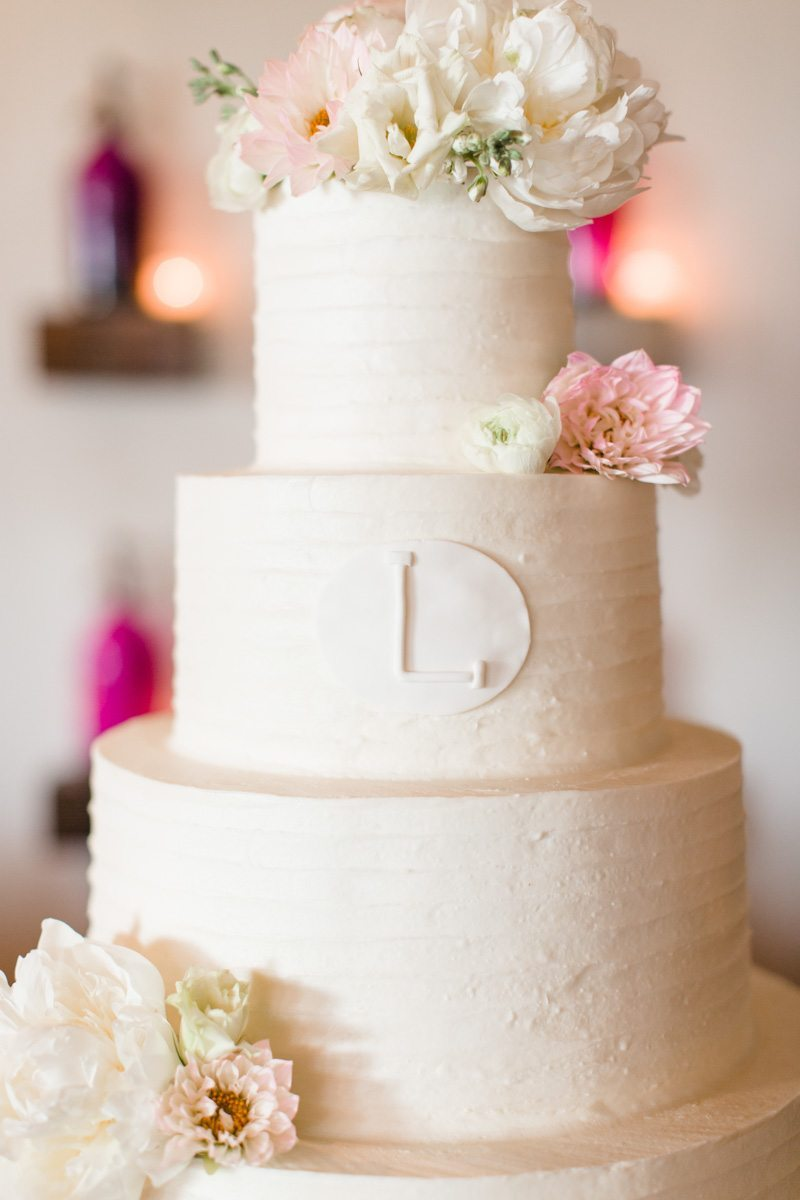 Closeup of white cake with D inscription and adorned with peonies