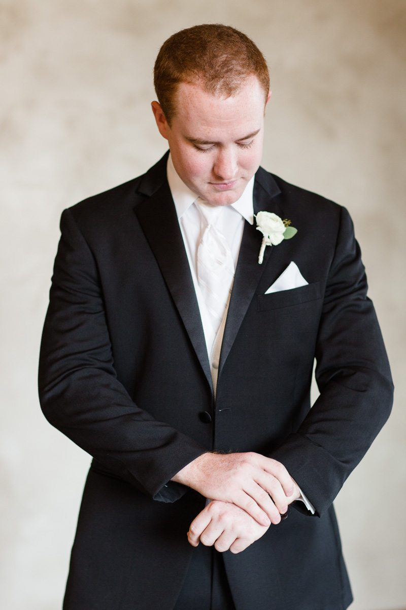 Groom in back suit and white tie