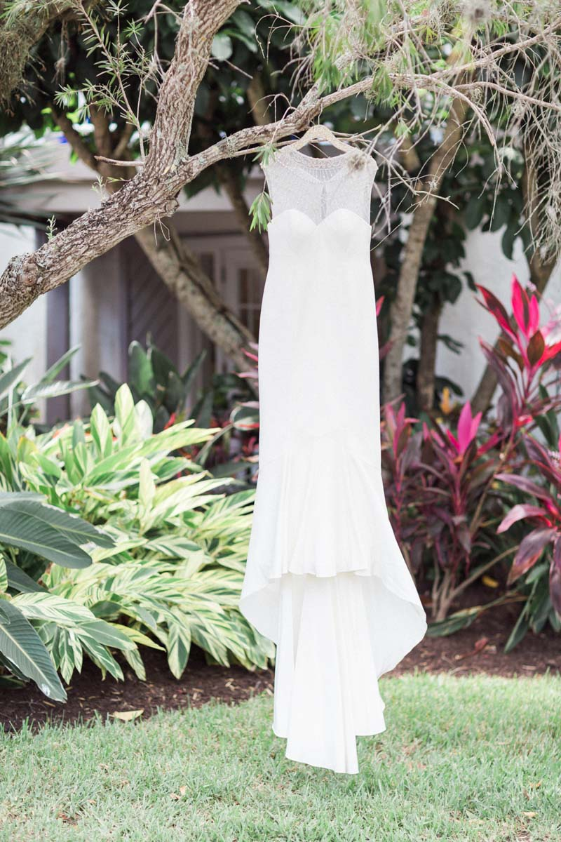 Illusion neckline detailed beading dress hanging from branch Mirtich_Scordos_Hunter_Ryan_Photo_sanibelislandcasaybelweddingphotographyhunterryanphoto7632