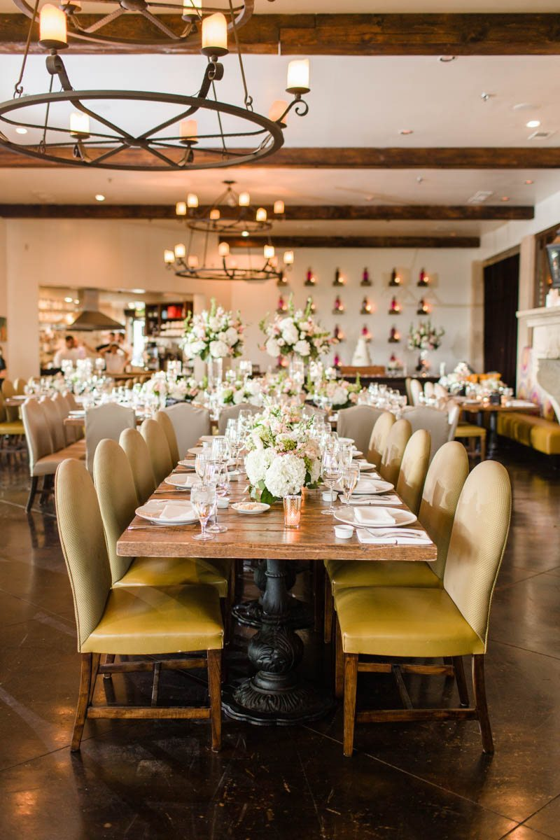 Indoor reception table with yellow chairs and floral centerpieces