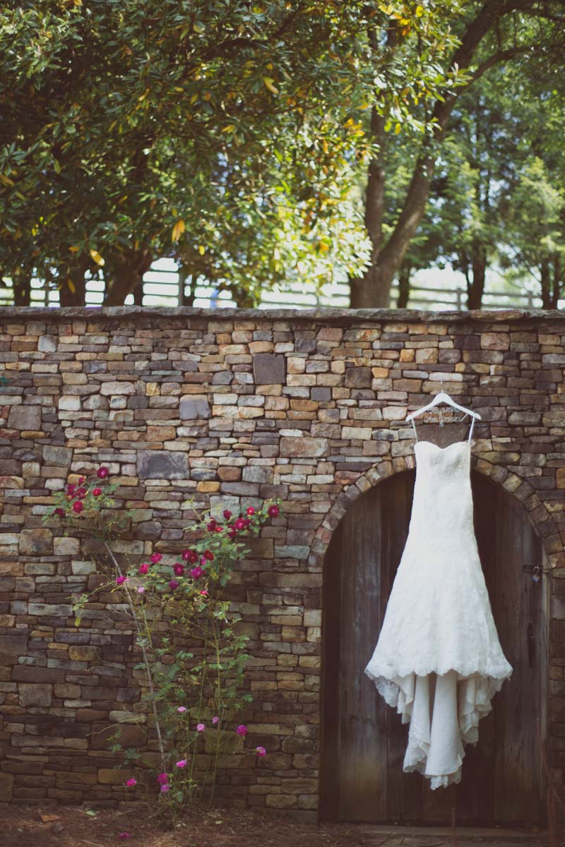 Lace strapless fit and flare gown hanging on stone bridge Ley_Green_Kelly_Anne_Photography_05089404