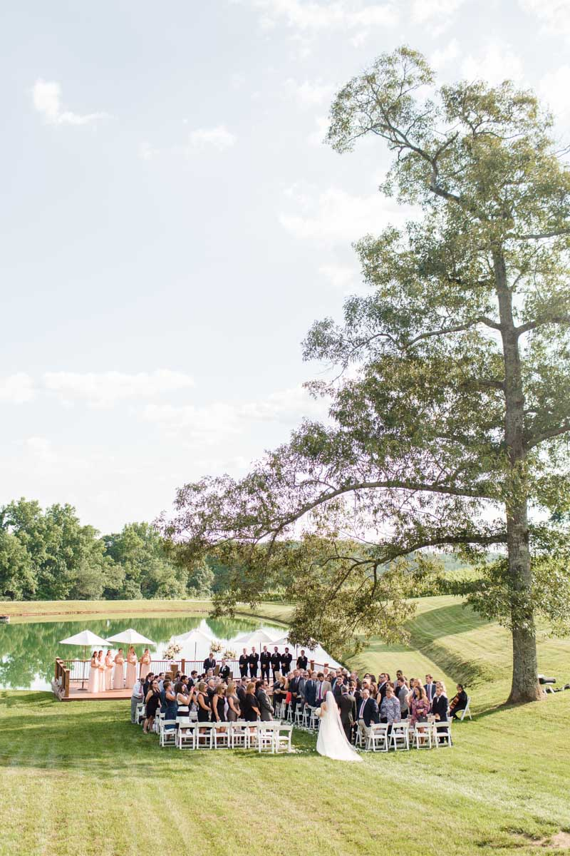 Long shot of Bride walking up the aisle during outdoor ceremony