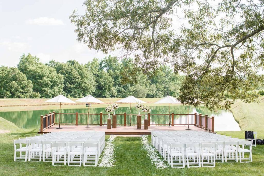Outdoor ceremony space with white garden chairs and rose petals, deck overlooking a lake