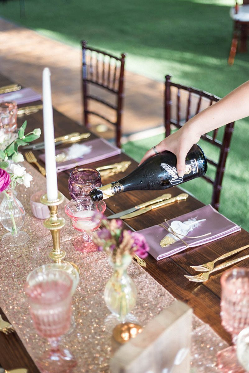 Pouring champaign into pink glass tall candel rose gold sparkle table runner Mirtich_Scordos_Hunter_Ryan_Photo_sanibelislandcasaybelweddingphotographyhunterryanphoto6176