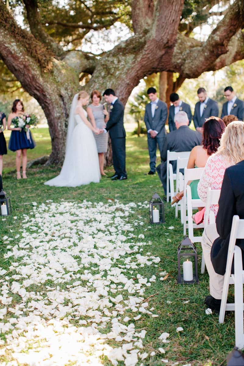 Praying during ceremony focus on white rose petals Hunter_Gibney_Ais_Portraits_AisPortraitsGibneyRibaultWedding351