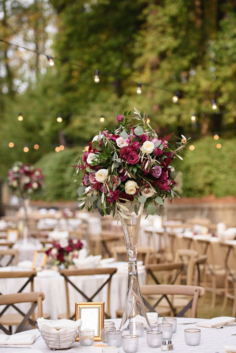 Reception table tall vace red and pink flowers string lighting back ground Schraudenbach_Rector_Laura_Stone_20151024010682