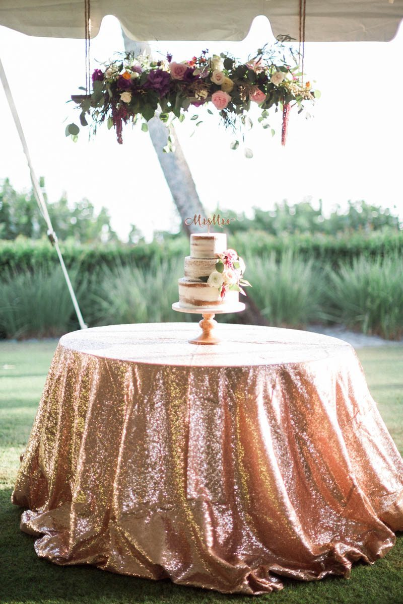 Rose gold glitter cake table linen floral banner over cake Mirtich_Scordos_Hunter_Ryan_Photo_sanibelislandcasaybelweddingphotographyhunterryanphoto8729