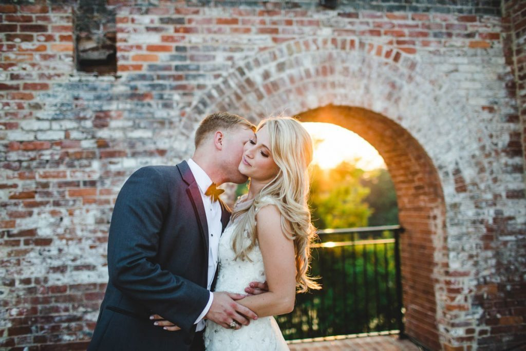Sunset behind brick structure groom kissing bride eyes closed ErinStephan_512