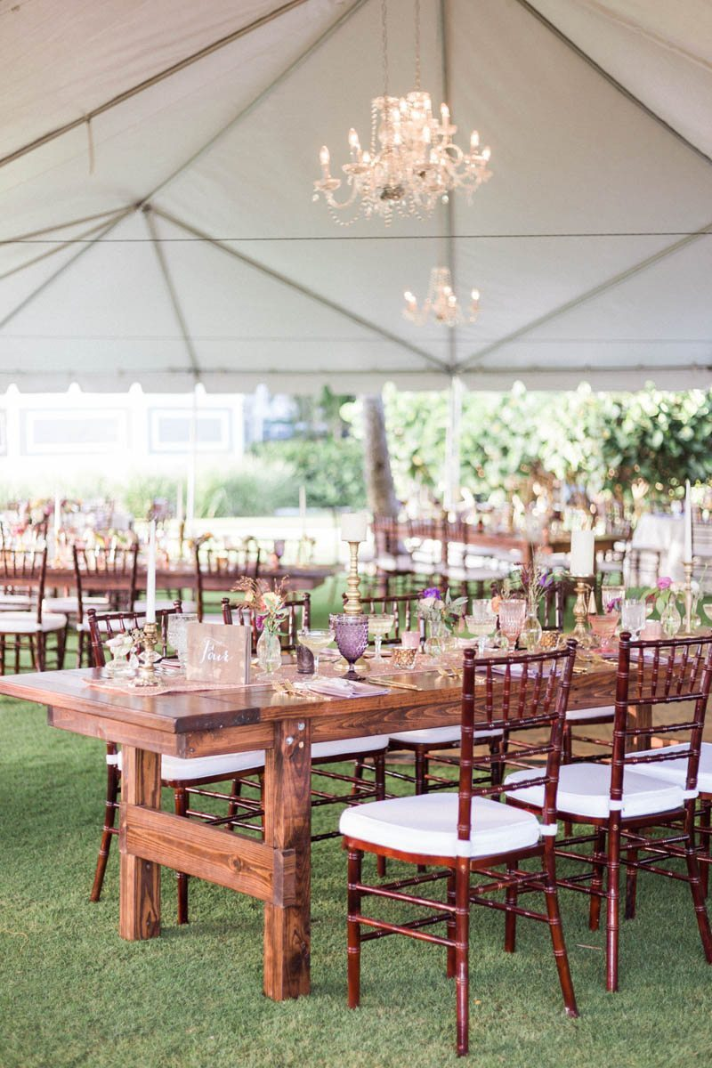 Tent overview chandelier wooden farm tables on grass Mirtich_Scordos_Hunter_Ryan_Photo_sanibelislandcasaybelweddingphotographyhunterryanphoto6205