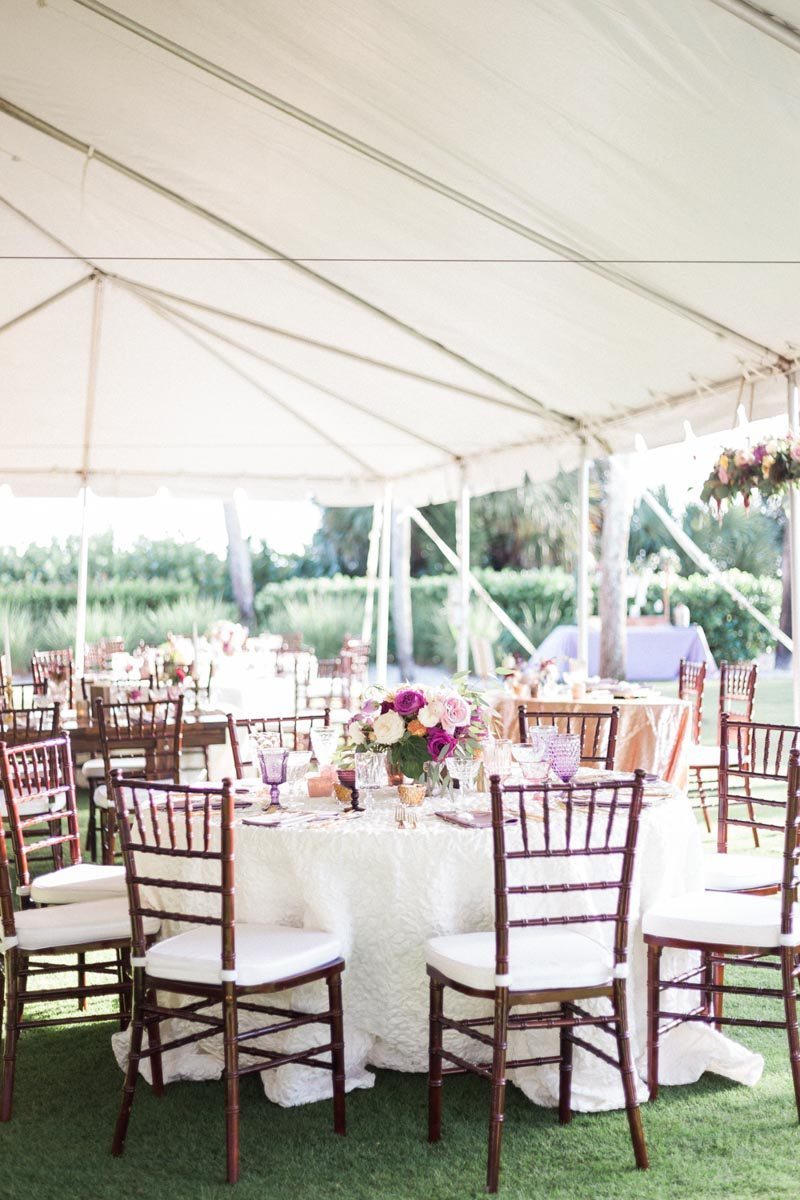 Tent under overview brown chilvari chairs white linens plum flower center pieces Mirtich_Scordos_Hunter_Ryan_Photo_sanibelislandcasaybelweddingphotographyhunterryanphoto6041