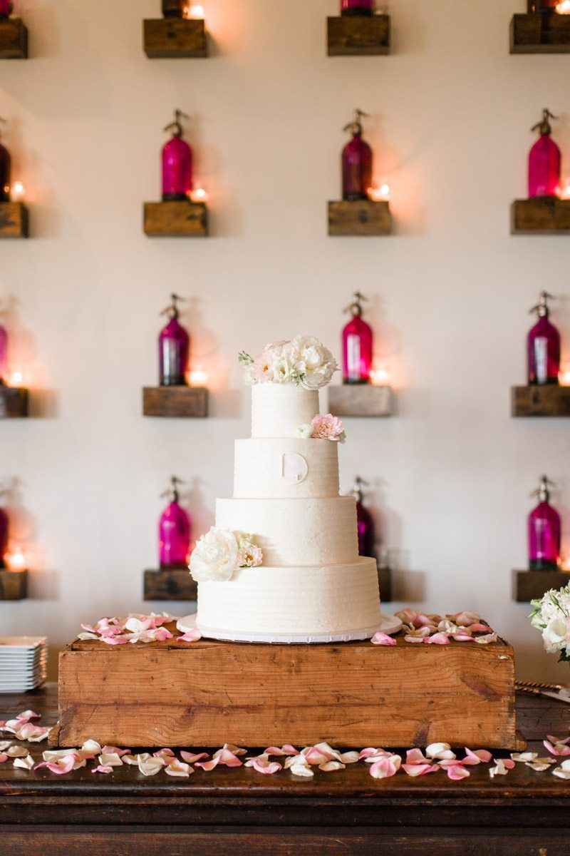 White cake with peony adronments on wooden stand with flower petals