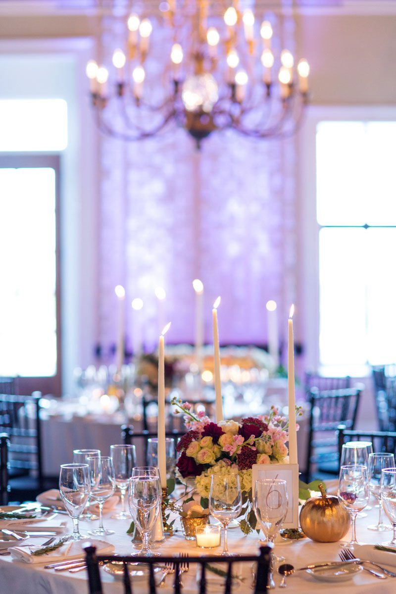 reception space details flower centerpieces tall candles and chandellier in background jadematthew_savannah_vics_57