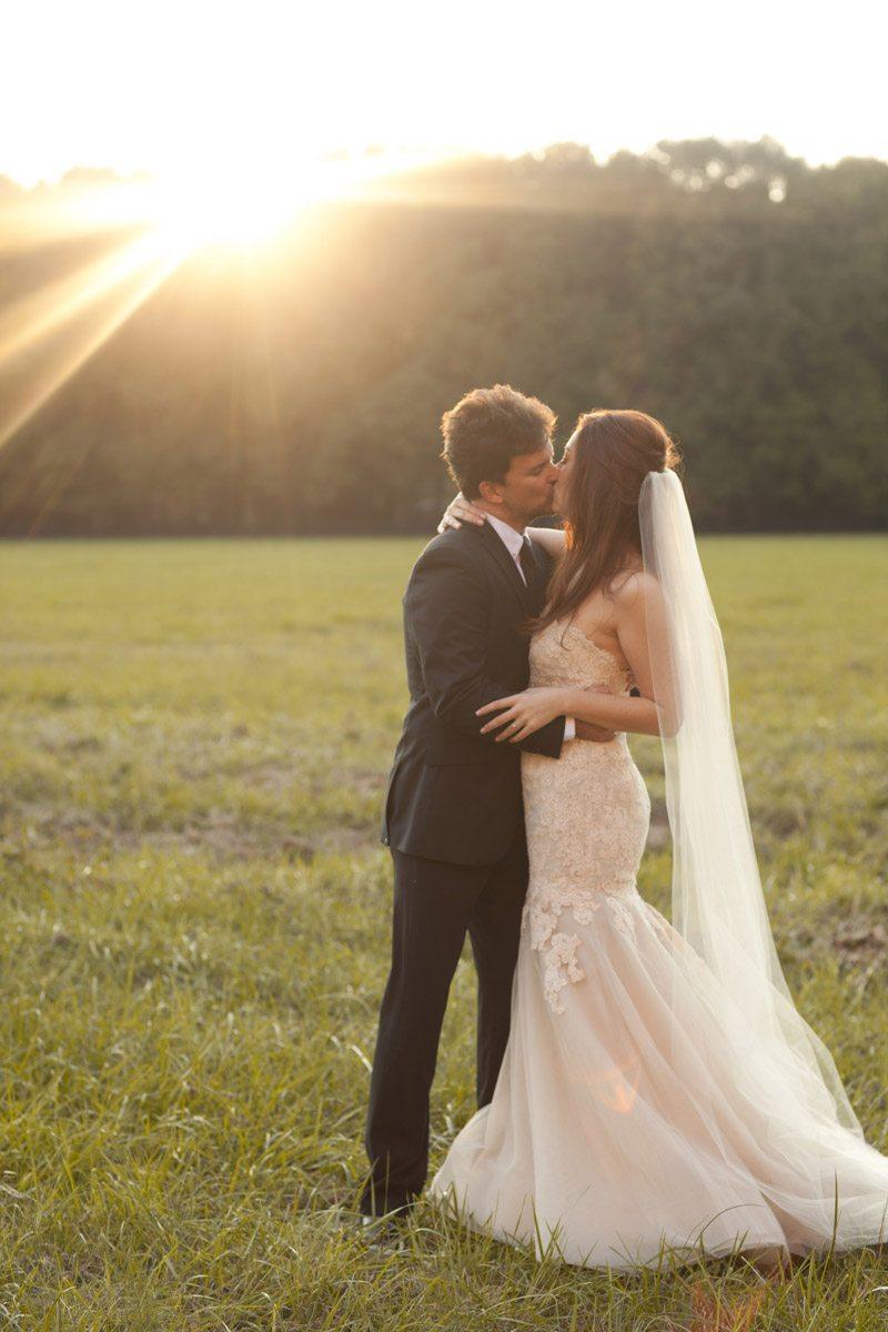 Bride and Groom Kissing in Field - Love Like Wedding