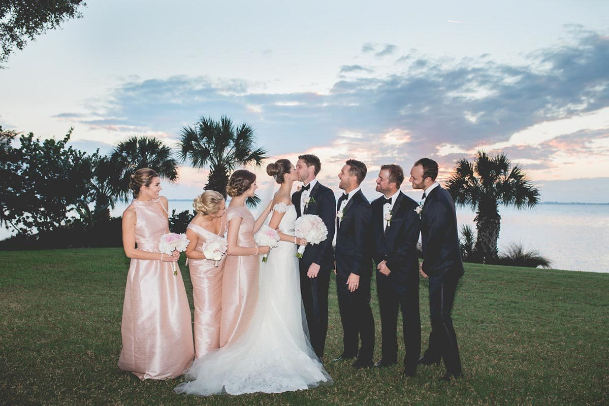 Bride and groom kissing with bridal party - Tara Tomlinson Photography