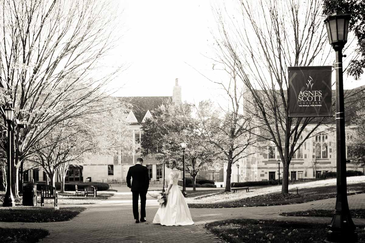 Bride and groom walking with agnes scot sign Beavor_Case_Sharon_Theresa_Wheaton_20151114sharontheresawheaton1057