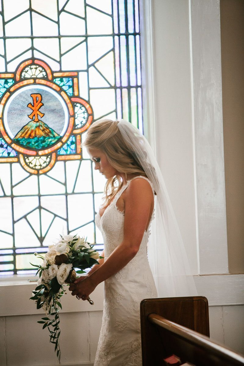 Bride praying in front of stain glass window with bouquet in hand