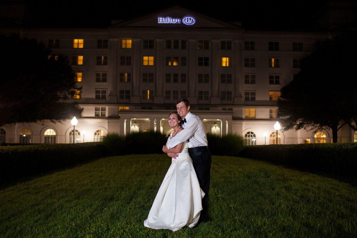 _Husband and wife in front of hilton hotel sign_Herndon_Herndon_Sharon_Theresa_Wheaton_20150627sharontheresawheaton1094