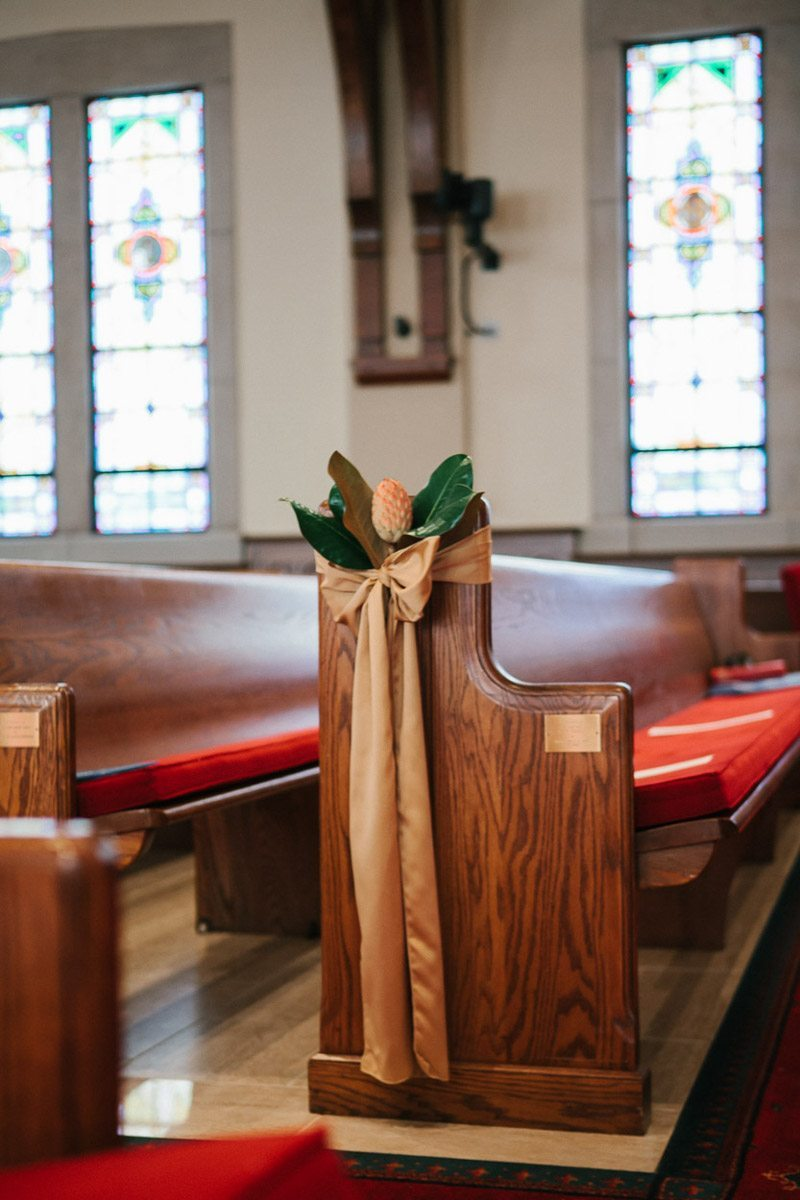 Wooden church pews with foral and ribbon adornments