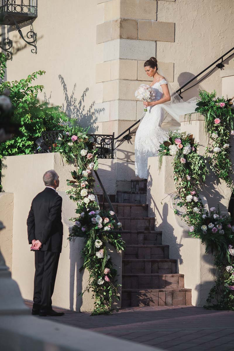 bride descending stone staircase to father - Tara Tomlinson Photography