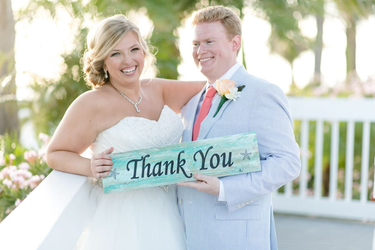 Bride and groom holding teal thank you sign Pearl_Warnock_Caroline__Evan_Photography_MichaelaChrisWedding1616