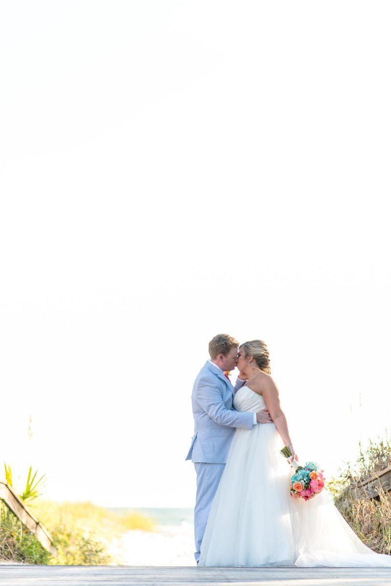 Bride and groom kissing by beach Pearl_Warnock_Caroline__Evan_Photography_MichaelaChrisWedding1528