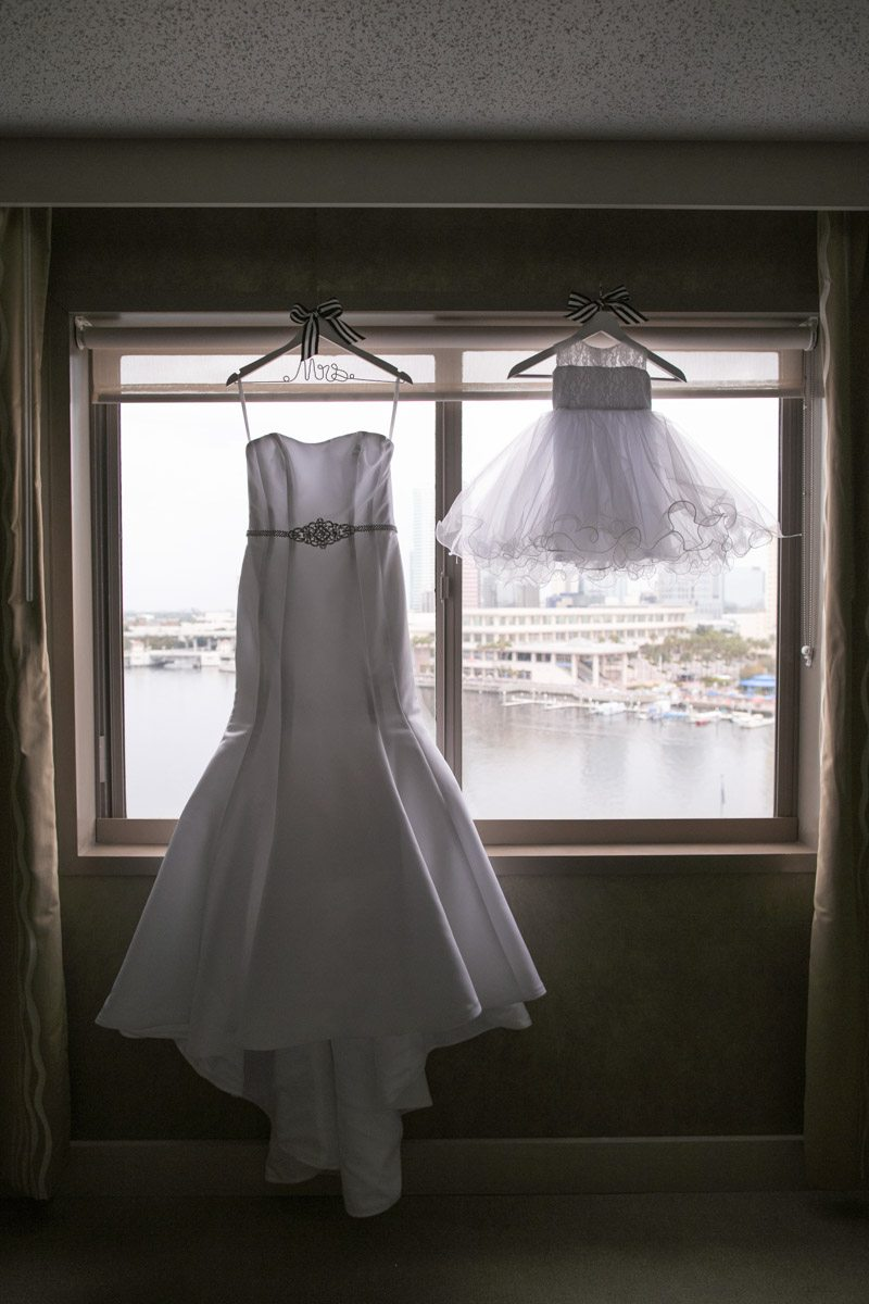 Bride's dress and flower girl dress hanging in window Wilcox_Soplinski_Carrie_Wildes_Photography_CWP0341